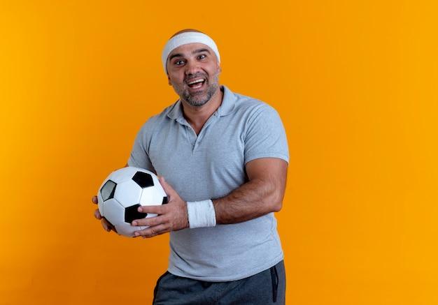 Uomo sportivo maturo in fascia tenendo il pallone da calcio guardando in avanti con il sorriso sul viso in piedi sopra il muro arancione 2