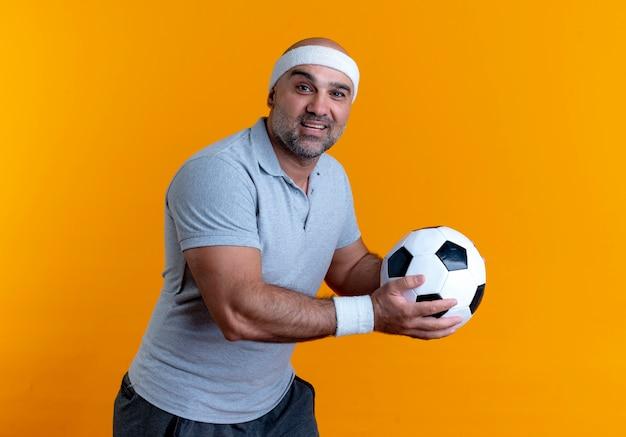 Uomo sportivo maturo in fascia tenendo il pallone da calcio guardando in avanti con il sorriso sul viso in piedi sopra la parete arancione