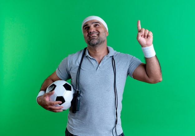 Mature sporty man in headband holding soccer ball pointing up with finger having new idea standing over green wall