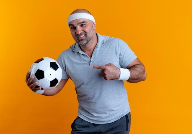 Maturo uomo sportivo in fascia tenendo il pallone da calcio puntando il dito verso di esso guardando in avanti con il sorriso sul viso in piedi sopra la parete arancione