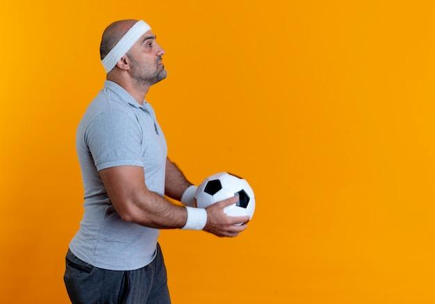 Uomo sportivo maturo in fascia tenendo il pallone da calcio in piedi lateralmente con la faccia seria sopra la parete arancione