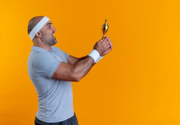 Uomo sportivo maturo in fascia che tiene il trofeo in piedi felice ed emozionato sopra la parete arancione
