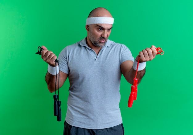 Maturo uomo sportivo in fascia tenendo due corde per saltare guardandoli confusi avendo dubbi in piedi sopra la parete verde