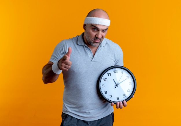 Mature sporty man in headband holding wall clock pointing with finger to the front with frowning face standing over orange wall