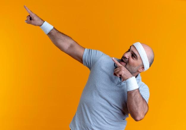 Uomo sportivo maturo in fascia cercando fiducioso che punta con le dita al lato in piedi sopra la parete arancione