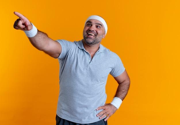Maturo uomo sportivo in fascia cercando sorridente fiducioso puntando con il dito a lato in piedi sopra la parete arancione