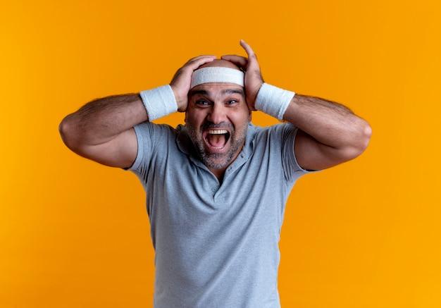 Uomo sportivo maturo in fascia guardando in avanti pazzo felice tenendo la testa con le braccia in piedi sopra la parete arancione