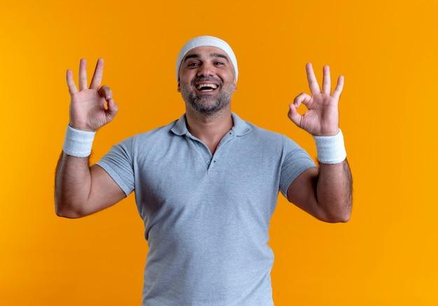 Maturo uomo sportivo in fascia guardando in avanti mostrando segno ok con entrambe le mani in piedi sopra la parete arancione