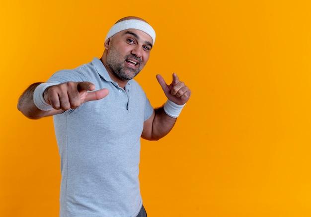 Maturo uomo sportivo in fascia guardando in avanti sorridente fiducioso che punta con le dita indice verso la parte anteriore in piedi sopra la parete arancione