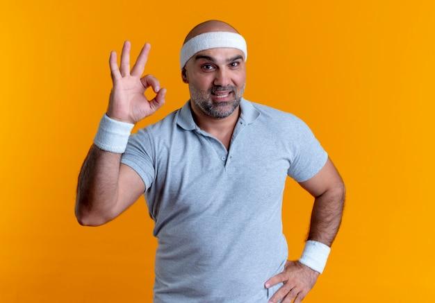 Uomo sportivo maturo in fascia guardando in avanti sorridente che mostra segno giusto in piedi sopra la parete arancione