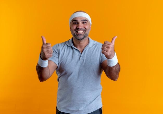 Uomo sportivo maturo in fascia guardando in avanti sorridendo con la faccia felice che mostra i pollici in su in piedi sopra la parete arancione