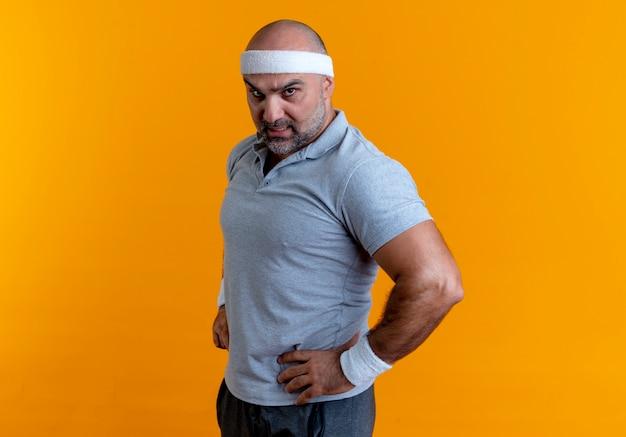 Uomo sportivo maturo in fascia guardando in avanti con le braccia ai fianchi con la faccia seria in piedi sul muro arancione