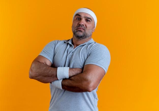Uomo sportivo maturo in fascia guardando in avanti con le mani incrociate sul petto con espressione seria in piedi sopra la parete arancione