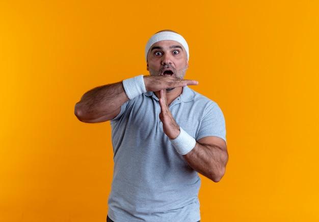 Maturo uomo sportivo in fascia guardando in avanti preoccupato rendendo il gesto di time out con le mani in piedi sopra la parete arancione