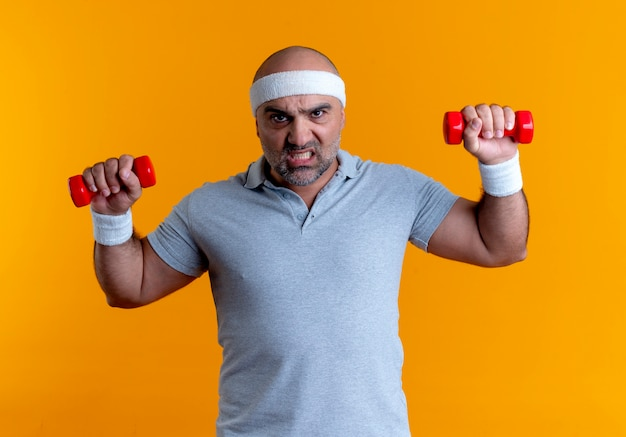 Mature sporty man in headband looking strained and confident working out with dumbbells standing over orange wall 2