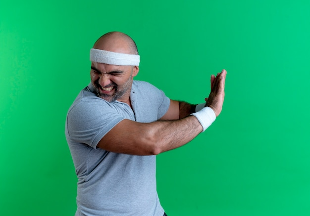 Mature sporty man in headband making defense gesture with hands with disgusted expression standing over green wall