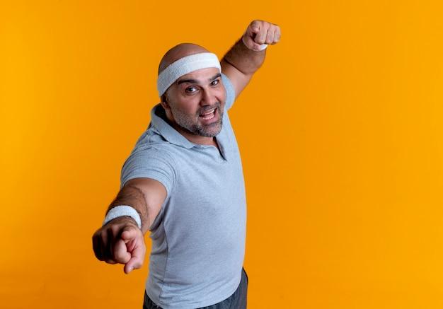 Maturo uomo sportivo in fascia che punta con il dito verso la parte anteriore alzando il pugno guardando fiducioso in piedi oltre la parete arancione
