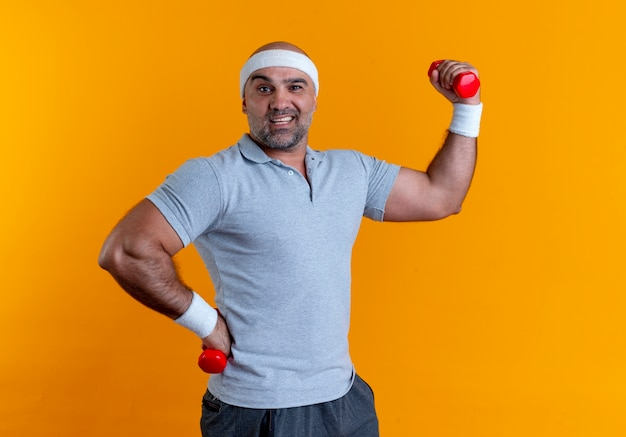 Maturo uomo sportivo in fascia alzando la mano con il manubrio guardando in avanti sorridente fiducioso in piedi oltre la parete arancione