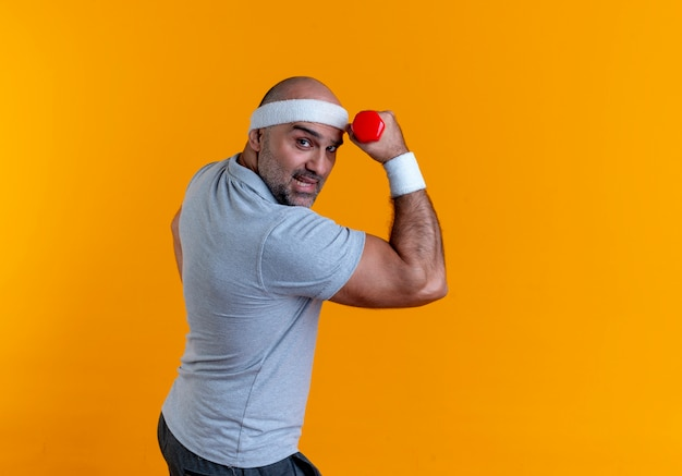 Mature sporty man in headband raising hand with dumbbell looking strained and confident standing over orange wall