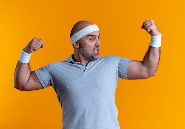 Uomo sportivo maturo nella fascia che solleva le mani che mostrano i bicipiti, concetto del vincitore che sta sopra la parete arancione