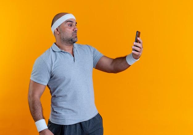 Maturo uomo sportivo in archetto tenendo selfie utilizzando il suo smartphone cercando confuso in piedi sopra la parete arancione