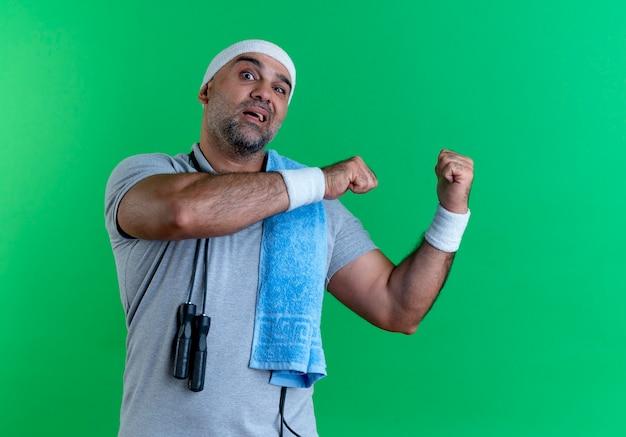 Uomo sportivo maturo in fascia con un asciugamano intorno al collo guardando in avanti confuso che punta indietro in piedi sopra la parete verde