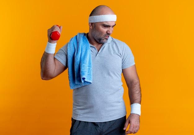 Uomo sportivo maturo nella fascia che risolve con il dumbbell che sembra stanco ed esaurito in piedi sopra la parete arancione Foto Gratuite