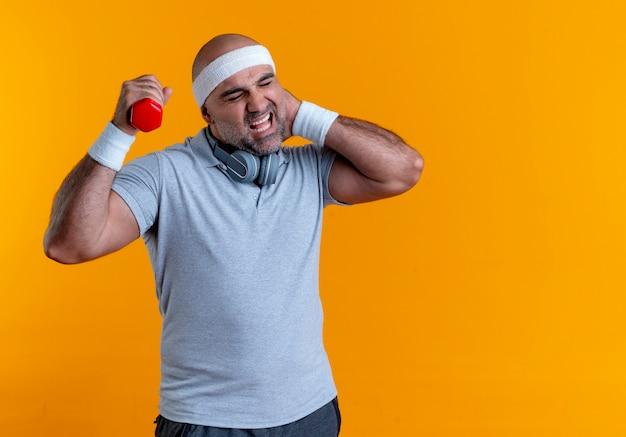Uomo sportivo maturo in fascia che risolve con il dumbbell che tocca il suo collo che ha dolore che si leva in piedi sopra la parete arancione