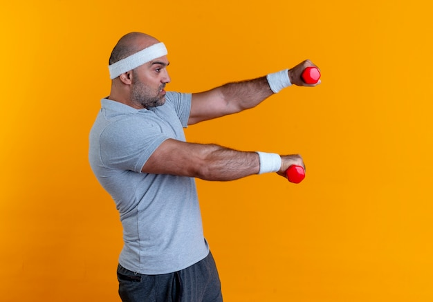 Uomo sportivo maturo in fascia che lavora fuori con i manubri che sembrano tesi e fiduciosi in piedi sopra il muro arancione 10