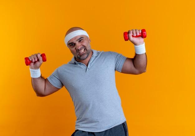 Uomo sportivo maturo in fascia che risolve con i dumbbells che sembrano tesi in piedi sopra la parete arancione