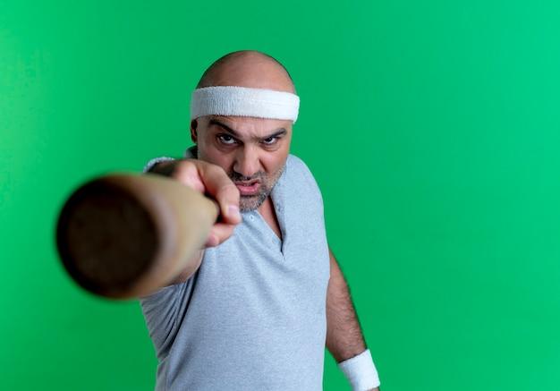 녹색 벽 위에 서있는 성난 얼굴로 앞을 가리키는 야구 방망이를 들고 머리띠에 성숙한 스포티 한 남자