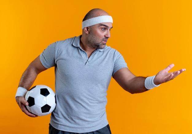 오렌지 벽 위에 서있는 것을 요구하거나 논쟁으로 팔을 옆으로보고 축구 공을 들고 머리띠에 성숙한 스포티 한 남자