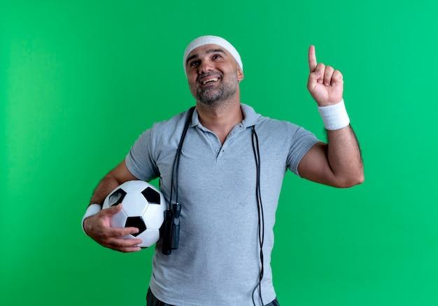 Зрелый спортивный мужчина в повязке на голову держит футбольный мяч, указывая пальцем, имея новую идею, стоя над зеленой стеной