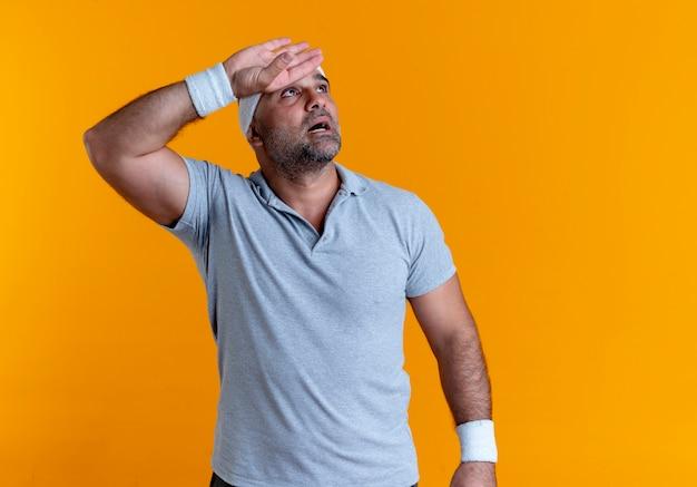 오렌지 벽 위에 서있는 운동 후 피곤하고 지쳐 보이는 머리 위로 손으로 제쳐두고 찾고 머리띠에 성숙한 스포티 한 남자