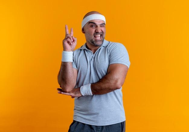 Зрелый спортивный мужчина в повязке на голову, глядя вперед, весело улыбаясь, показывает знак победы, стоящий над оранжевой стеной