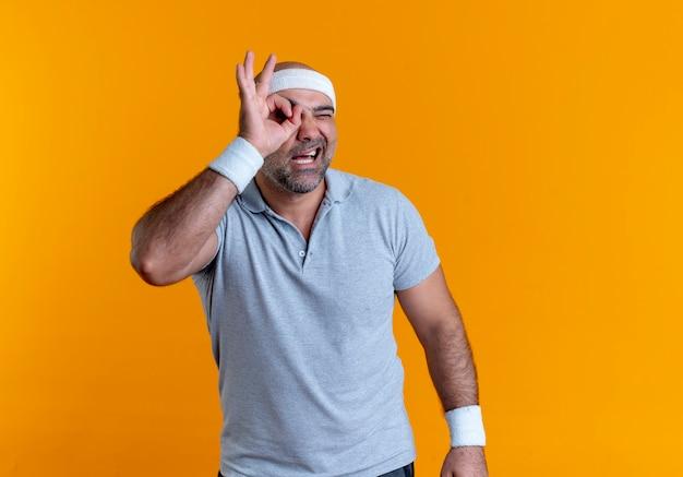 Зрелый спортивный мужчина в повязке на голову делает знак ок с пальцами, глядя сквозь этот знак, стоящий над оранжевой стеной