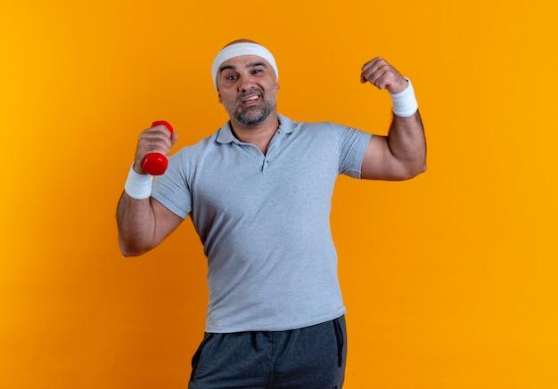 Зрелый спортивный мужчина в повязке на голову, поднимающий руку с гантелями, глядя вперед с уверенным выражением лица, улыбаясь, стоя над оранжевой стеной