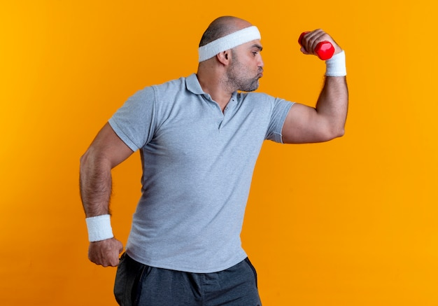 Зрелый спортивный мужчина в повязке на голову, поднимающий руку с гантелями, демонстрирует бицепс, уверенно глядя, стоя над оранжевой стеной