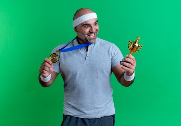 緑の壁の上に立って幸せで興奮してそれを見てトロフィーを保持している彼の首の周りに金メダルを持つヘッドバンドの成熟したスポーティな男