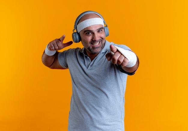 Зрелый спортивный мужчина в повязке на голову с наушниками на голове, указывая пальцем вперед, весело улыбаясь, стоя над оранжевой стеной