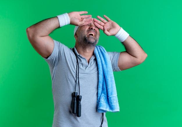 緑の壁の上に立っているイライラした表情で目を覆っている彼の首の周りにタオルでヘッドバンドの成熟したスポーティな男