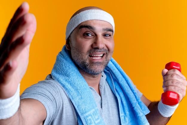 Зрелый спортивный мужчина в повязке на голову с полотенцем на шее, держащий гантель, глядя вперед с улыбкой на лице, стоящий над оранжевой стеной