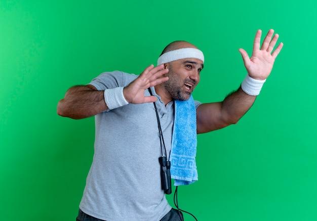 Зрелый спортивный мужчина в повязке на голову с полотенцем на шее, глядя с выражением страха, делая защитный жест руками, стоящими над зеленой стеной