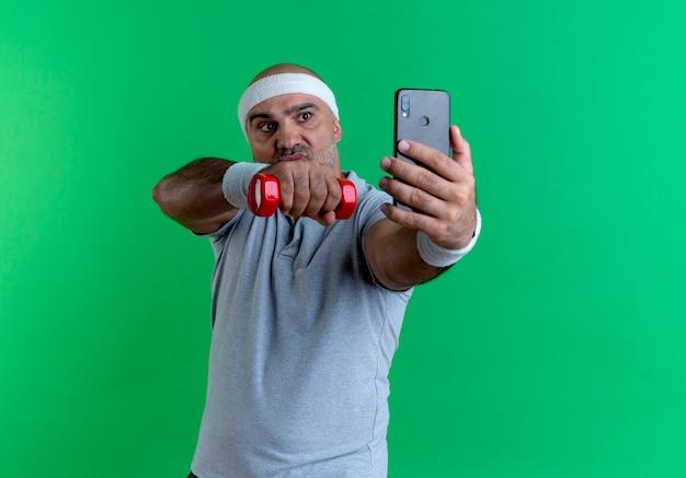 緑の壁の上に立っている真面目な顔で見ている彼のスマートフォンを使用してselfieを取るダンベルで手を上げる彼の首の周りにタオルでヘッドバンドの成熟したスポーティな男