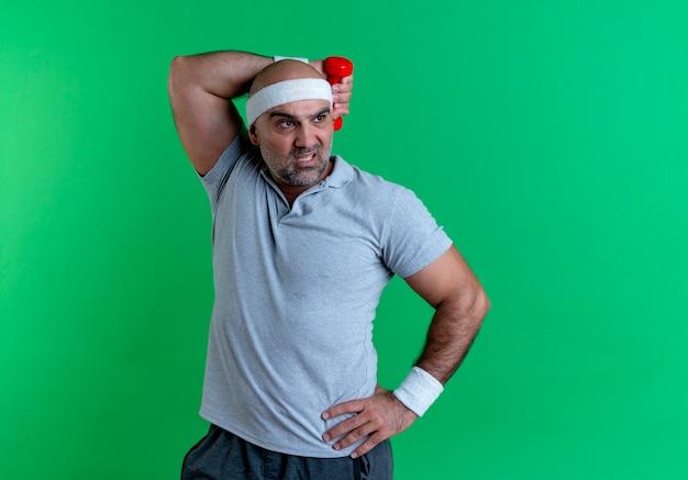 緑の壁の上に緊張して自信を持って立っているように見えるダンベルで運動するヘッドバンドの成熟したスポーティな男