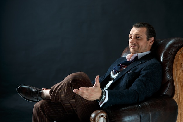 The mature stylish man in a suit on a gray studio. businessman sitting on an armchair