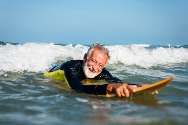 成熟したサーファーは波をキャッチする準備ができて