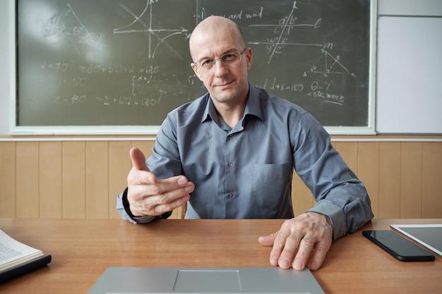 Зрелый учитель в рубашке и очках сидит за столом, смотрит на дисплей ноутбука перед ним и объясняет предмет на уроке в классе