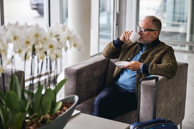 Зрелая туристка пьет кофе в зоне ожидания