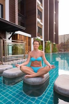 Зрелая туристическая женщина занимается йогой и медитацией рядом с бассейном